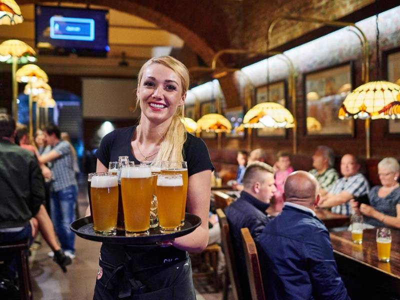 smiling waitress carrying plenty of beers